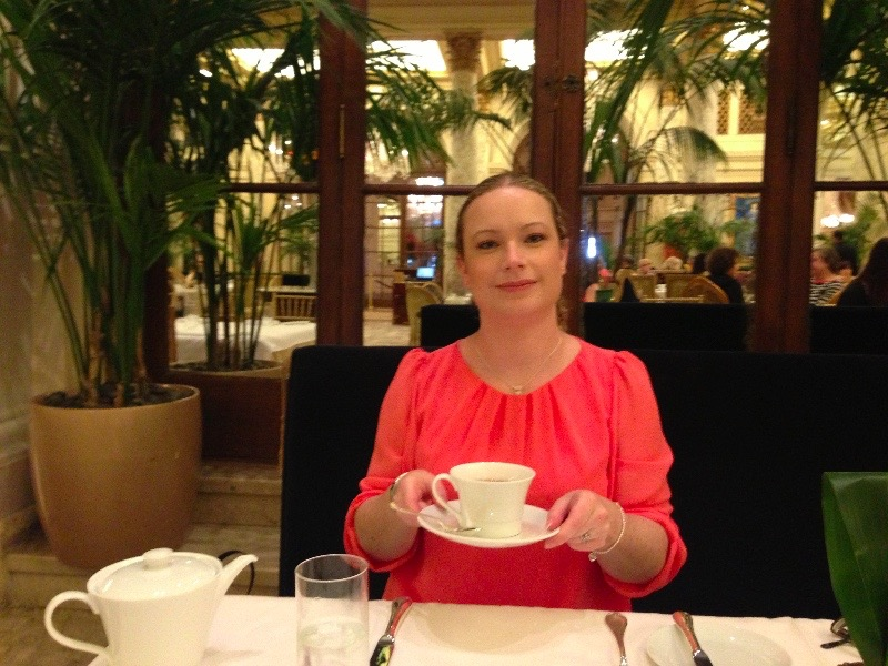 Rachael raising a cup of tea at New York Plaza Hotel Palm Court